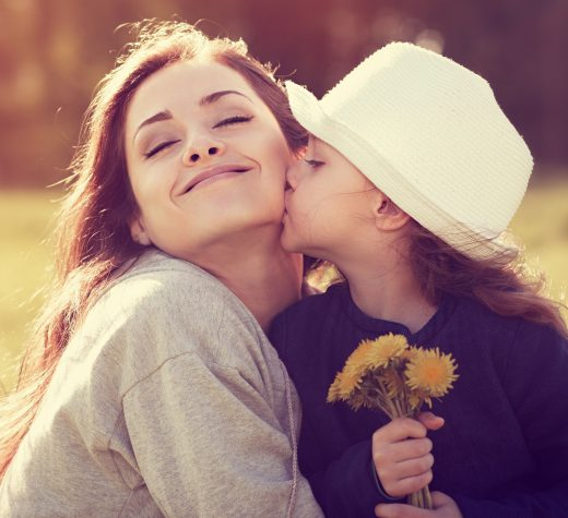 57247810 - happy daughter kissing her enjoying mother on summer sunny background
